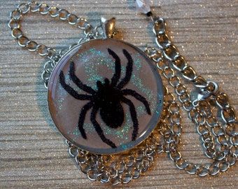 Black glitter spider pendant necklace on a taupe background sealed in clear resin // gifts for her // creepy cute // spider web // nu goth