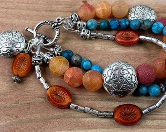 7 1/2 inch tangerine bracelet / orange and blue 3 strand bracelet with charms