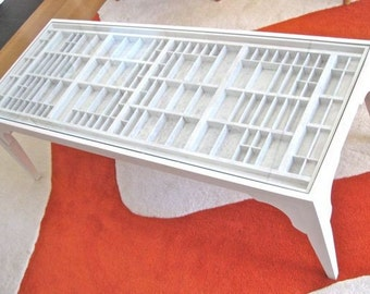 Large coffee table, white washed finish, with a glass table top that lifts out so you can display collectibles, seashells and more.