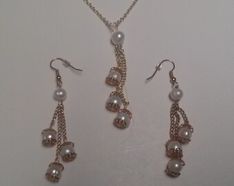 Set of necklace and earrings with three strands of freshwater pearls each on gold chains