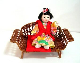 Oriental Doll on Wicker Bench