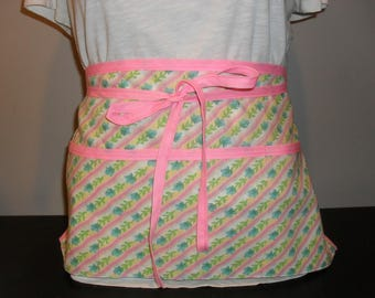 Waitress 3 pocket half apron. Rows of green flowers with pink trim.
