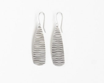 """Textured silver earrings in a long drop shape with a wavy pattern oxidized to catch the light and dark hanging - """"Soledad Earrings Silver"""""""