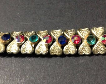 Coro light gold tone link bracelet with textured heart links and multi colored rhinestones (3 missing).