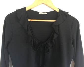 Black tie up front top. Frilled neckline. Frilly sleeves. Size S-M.