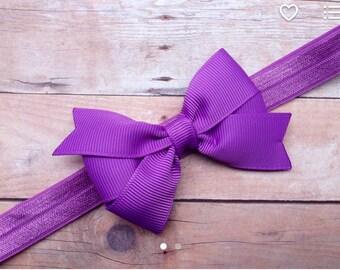 Purple 3 inch pinwheel style bow on matching elastic headband