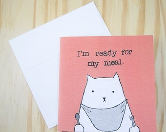 """CARD: """"Cat Demands Food"""" featuring a cat in a bib, holding cutlery, and waiting impatiently to be fed"""
