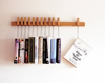 Custom made wooden book rack / bookshelf in Oak. The pins are also bookmarks.