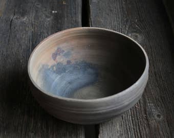 Terracotta folksy bowl. Medieval Russian style dish. Wabi-Sabi, unglazed, old fashioned way, wood-fired rustic pottery.