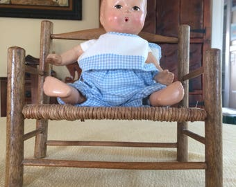 ANTIQUE DOLL with hand painted face, blue & white checkered outfit and vintage wool/wicker love seat.