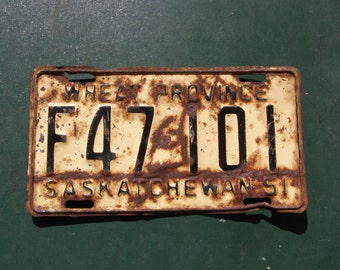1951 Saskatchewan Farm Vehicle License Plate That is Banged Up and Rusty In All The Right Places
