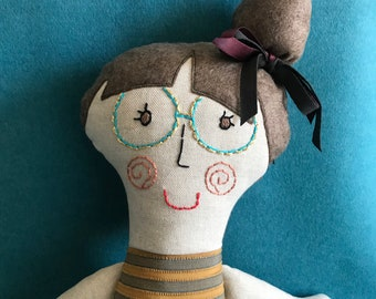 Doll made of handmade fabric with embroidered glasses