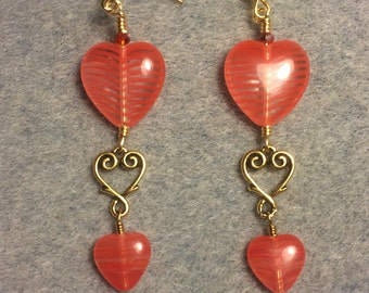 Large and small matching orange red Czech glass heart bead dangle earrings joined by a gold Tierracast heart connector charm.
