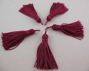 A cranberry color rayon thread tassel