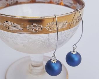 Iridescent blue Swarovski pearl earrings on long sterling silver hooks.