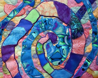 A wall hanging  art quilt in deep blue, peach and purple abstract spirial