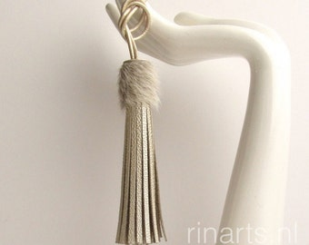 Tassel bag charm in champagne leather with a stingray embossed print and cow hair top.  Tassel purse charm