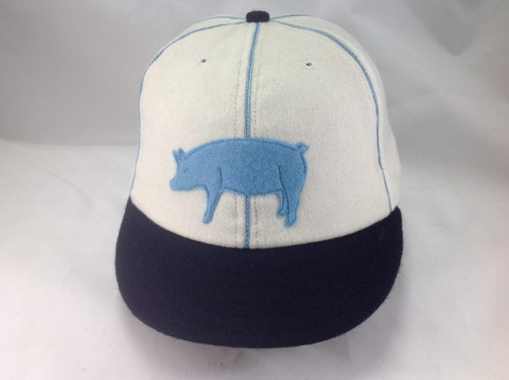 """Hog-n-Hominy Vintage Base Ball team cap. White wool cap and  navy 2"""" visor and button. Baby blue hog and soutache. Select size at checkout"""