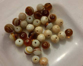 set of 35 ecru and amber colored glass beads. 8mm in diameter