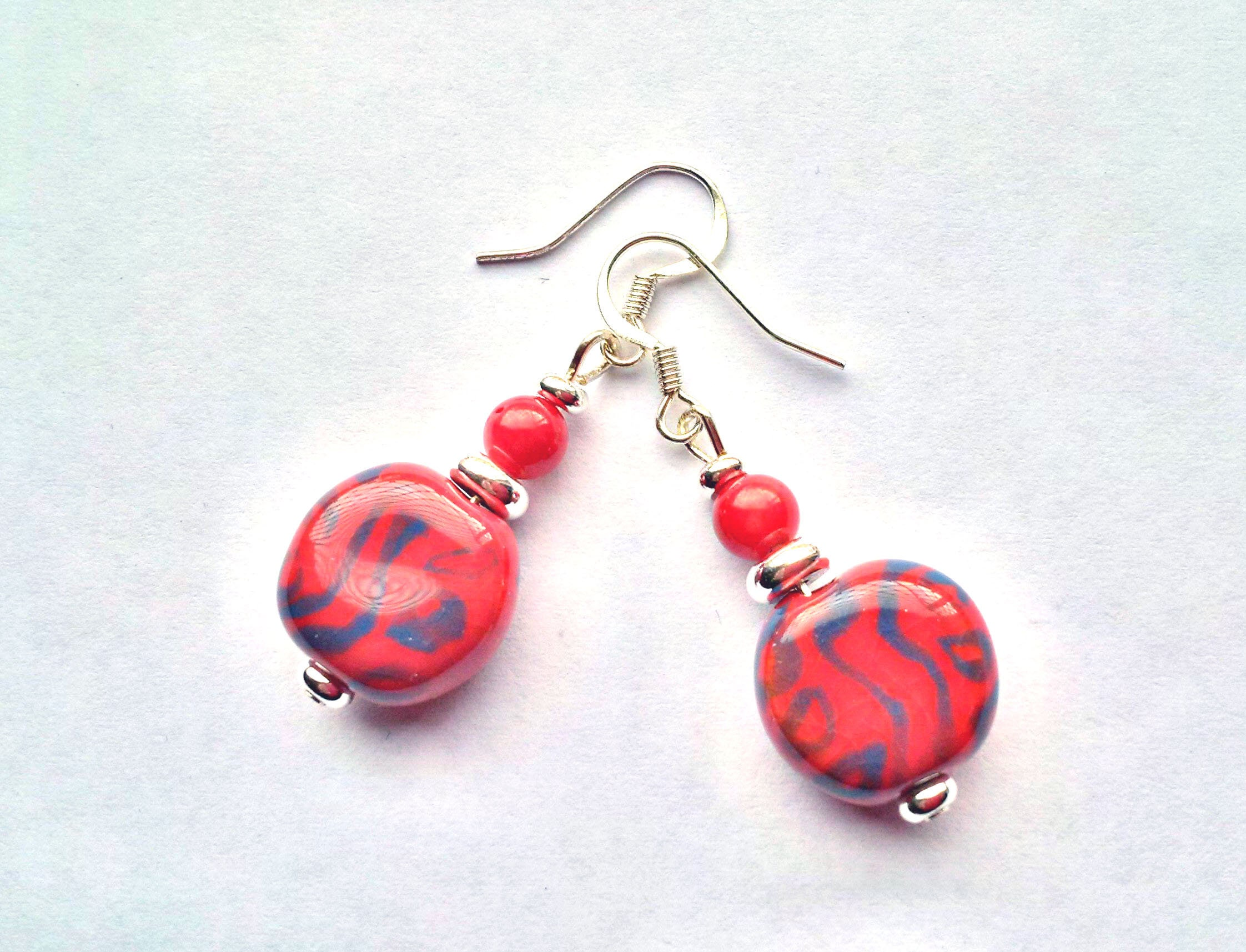 Red and blue patterned ceramic earrings made from Kenyan Kazuri fair trade, hand made and hand painted beads