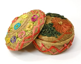Two Hand Woven Straw Baskets with Lids Featuring Raffia Floral Decoration