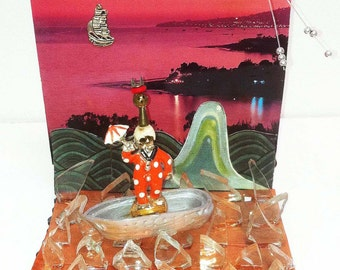 Surreal diorama,DennisWilson,Live in Bliss,miniature surreal art,clown with umbrella in boat,glass seascape,glass sea, surrealism,clown with