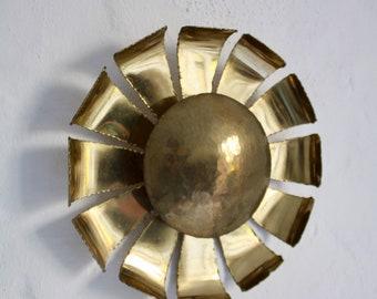 A fantastic sun-shaped flamecut brass sconce