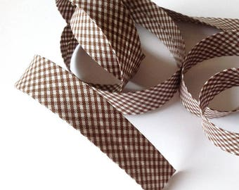 Pre-folded cotton bias has checkered chocolate brown gingham sold by the yard