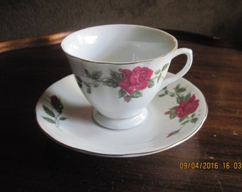 dainty bone china teacup and matching saucer, marked, made in china,pink roses hand painted on both ,gold trim