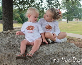 Hook 'Em Horns! Short sleeve t-shirt embroidered with a football applique in Texas colors and a polka dot bow.