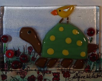 Cute turtle and his friend the yellow bird.  3D mixed media fused glass and watercolor painting in shadowbox.