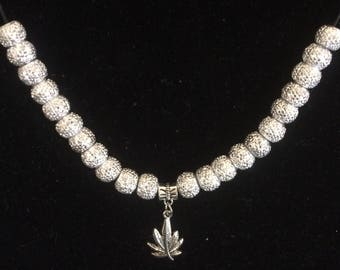 Silver-toned choker with one leaf.