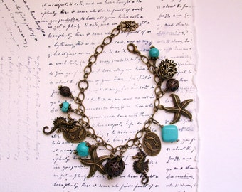 Sea horse bracelet with starfish and other decorative charms. 4 turquoise hand wrapped beads accent the antiqued bronze bracelet.