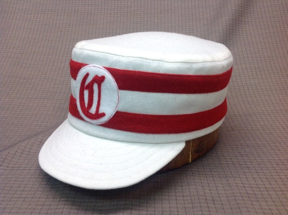 Warm white wool flannel box cap with red wool bands and felt logo, embroidered back. Any size or logo available