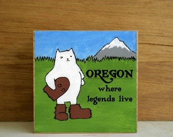 "ART BLOCK: ""Oregon Cat"" featuring a Winking Cat in a Sasquatch or Big Foot Costume and Mt. Hood"