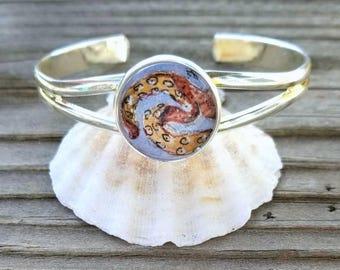 Tentacles bracelet. Hand painted mini illustration of orange tentacles in silver plated adjustable cuff. Octopus bracelet, kraken bracelet