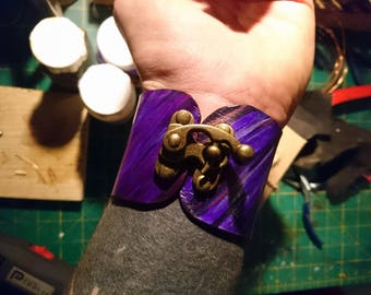 Odd shaped purple leather cuff.