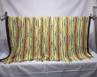 Vintage afghan blanket done in green, yellow, orange, browns and white brown in a striped and diamond pattern, handmade,