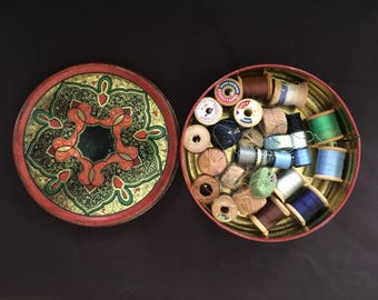 vintage tin with sewing threads on wooden spools