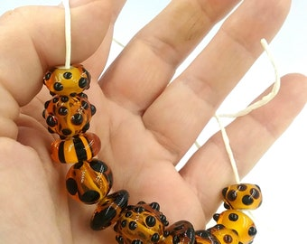 11 Amber  and black Italian glass small beads