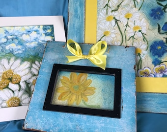 A group of 3 framed fiber art quilts, in a beachy cottage style. A daisy theme unites them. The colors are blue, yellow & white.