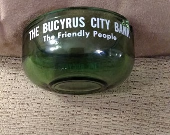 Green glass vintage ashtray. Four inches across by two inches deep. From the Bucyrus City Bank, the friendly people.
