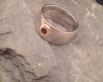 Simple Solitaire ring made of silver 935er and gold version 585er with garnet