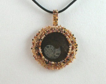 Necklace  Ammonite seed bead emboidered with tan, brown seed beads on a faux leather cord