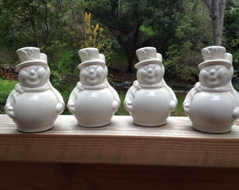Vintage set of four jolly white snow men with top hats and brooms.