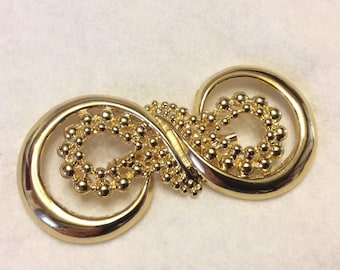 Designer signed VAl gold toned metal figure 8 brooch pin. Free ship to US
