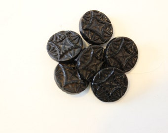 Eleven black glass vintage buttons.
