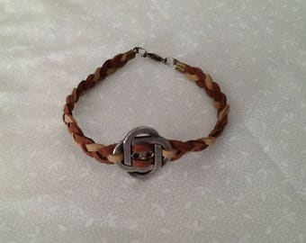 Faux Suede braided bracelet with a center metal charm.
