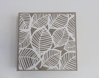 Table leaves on natural linen. 20 X 20 cm. Paper cut, kirigami