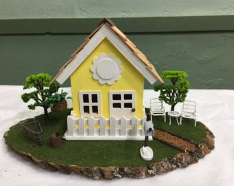 Diorama of cottage with lawn chairs and mailbox